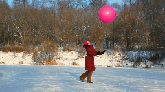 Smiling woman throws up air-balloon in snowfield Stock Footage