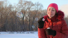 Portrait of woman inflates soap bubbles in wintry snowfield Stock Footage