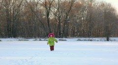 Little girl runs to camera in wintry park Stock Footage