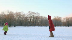 Mother rotates with her daughter in snowfield Stock Footage