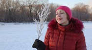 Portrait of woman blows to branchlet covered with hoarfrost Stock Footage
