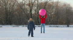 Father and son plays with air-balloon in snowfield Stock Footage