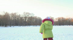 Girl runs from camera in wintry snowfield, and comes back Stock Footage