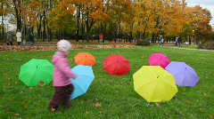 Boy and girl runs about umbrellas in autumn park Stock Footage