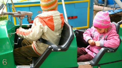 Boy and girl sits in dodgem in city park amusement Stock Footage