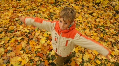 boy rotates against grass and fall foliage - stock footage