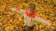 Stock Video Footage of boy rotates against grass and fall foliage