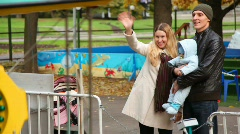 Happy family with baby stands in amusement park Stock Footage