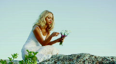 Woman on a rock against the sky Stock Footage