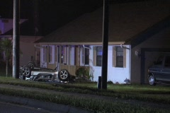 Overturned vehicle in front lawn wide - stock footage