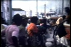 Crowd waits for Fisherman to unload boat in Nassau Stock Footage