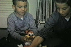 Brothers play with Woody Woodpecker and Mousetrap board game Stock Footage
