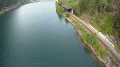 Aerial, flight over railway and mountain lake, very wide, low level Stock Footage