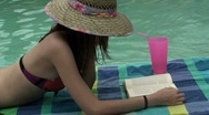 Stock Video Footage of Woman Reads Drinks By Pool