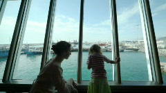 Mother with daughter looks at ship in sea port Stock Footage