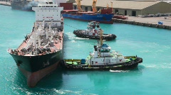 Two towing boats rotates tanker in sea port Stock Footage