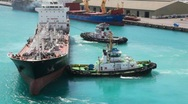 Stock Video Footage of two towing boats rotates tanker in sea port
