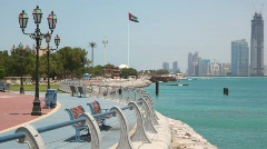 Sea shore with flag of United Arab Emirates, skyscrapers on background Stock Footage
