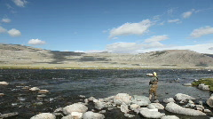 Fisherman with spinning catching fish in mountain river Stock Footage