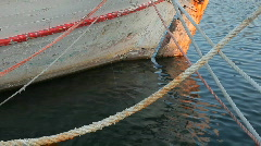 Crossed boat ropes and a hull of a used anchored white-red boat HD Stock Footage