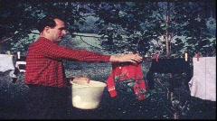 Man picks washing from line (vintage 8 mm amateur film) Stock Footage