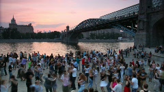 Dancing people on the square near the bridge. Stock Footage