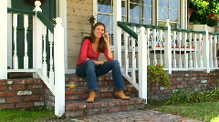 Young woman talking on cell phone while sitting on front porch Stock Footage