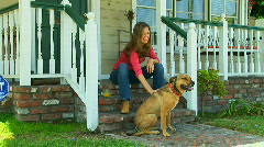 Young woman sitting on front porch petting her dog Stock Footage
