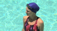 Portrait of young woman in pool with swim cap and goggles Stock Footage