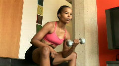Young African American woman lifting weights and exercising - stock footage