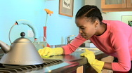 Stock Video Footage of Young African American woman cleaning countertop in kitchen
