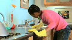 Young African American woman cleaning countertop in kitchen Stock Footage