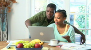 Stock Video Footage of Young African American couple using credit card on laptop
