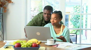Young African American couple using credit card on laptop Stock Footage