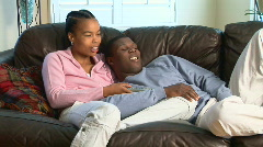 Young African American couple with remote watching TV Stock Footage