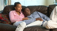 Stock Video Footage of Young African American couple with remote watching TV