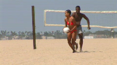 Young African American couple playing volleyball at the beach Stock Footage