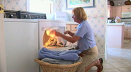 Stock Video Footage of Mature woman removing clothes from dryer