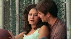 Young couple resting and talking by chain-link fence - stock footage