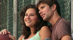 Young couple resting and talking by chain-link fence Stock Footage