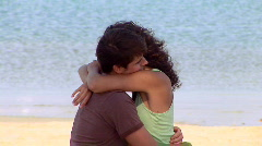 Young couple hugging and being affectionate by ocean - stock footage