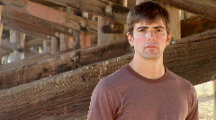 Portrait of serious young man outdoors by ocean pier Stock Footage