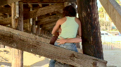Young couple being affectionate outdoors by ocean pier - stock footage