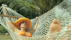Blond young woman relaxing on hammock Stock Footage