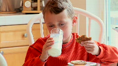Young boy eating cookies and milk Stock Footage