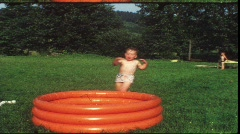 Toddler jumping in garden pool (vintage 8 mm amateur film) Stock Footage