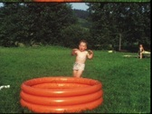 Stock Video Footage of Toddler jumping in garden pool (vintage 8 mm amateur film)