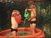 Stock Video Footage of Children splashing in garden pool (vintage 8 mm amateur film)