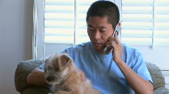 Young Asian man talking on phone with pet dog in lap - stock footage