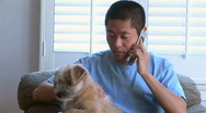 Stock Video Footage of Young Asian man talking on phone with pet dog in lap